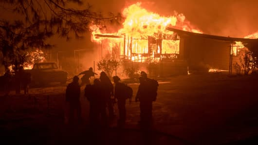 A firefighter carries a hose as a house burns in Oroville, California on July 8, 2017.