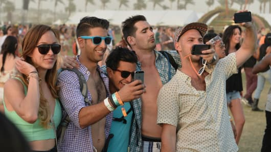 Music fans take selfies during day 2 of the 2014 Coachella Valley Music & Arts Festival at the Empire Polo Club on April 12, 2014 in Indio, California.