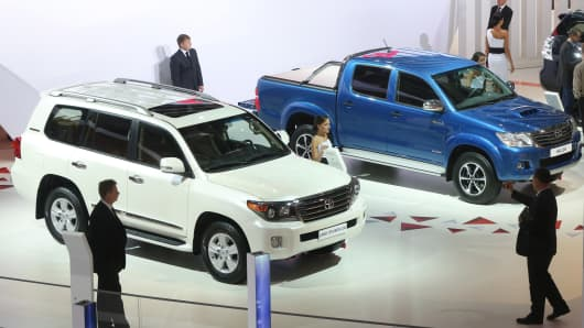 A Toyota Land Cruiser 200 sports utility vehicle (SUV) and a Toyota Hilux pickup truck sit on display.