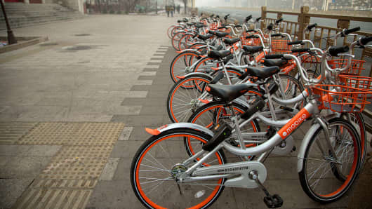 Bicycles belonging to bike-sharing company Mobike are lined up on a street in China on Jan. 1, 2017.