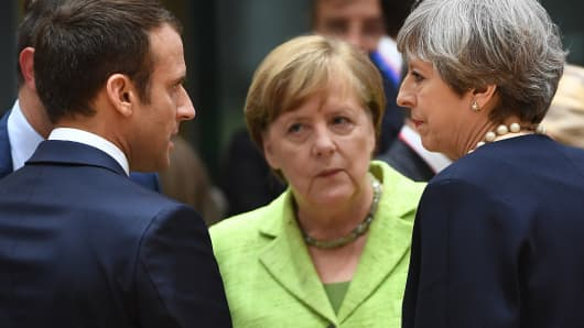 (From L) French President Emmanuel Macron, German Chancellor Angela Merkel and British Prime Minister Theresa May talk as they attend an European Union leaders summit, on June 22, 2017, at the European Council in Brussels.