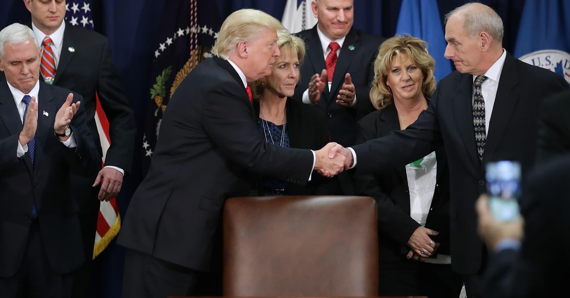 President Trump shakes hands with Homeland Security Secretary John Kelly