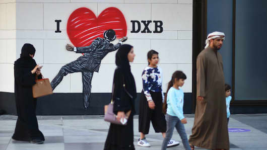 Pedestrians walk past street art in Dubai, United Arab Emirates.