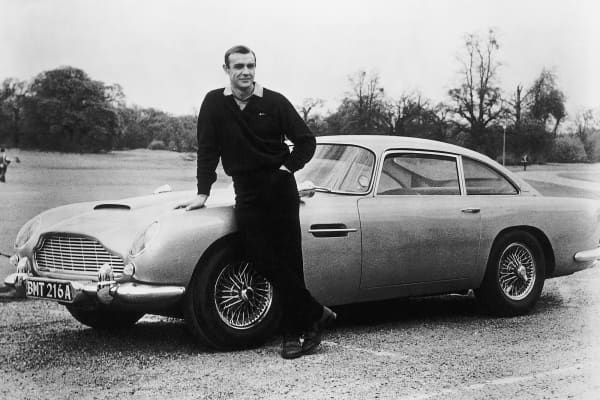 Actor Sean Connery, as James Bond, on the set of Eon Productions' Goldfinger with a 1964 Aston Martin DB5