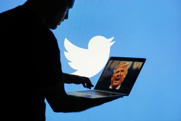 A man holds a laptop showing an image of US president Donald Trump with a Twitter logo displayed in the background in this photo illustration.