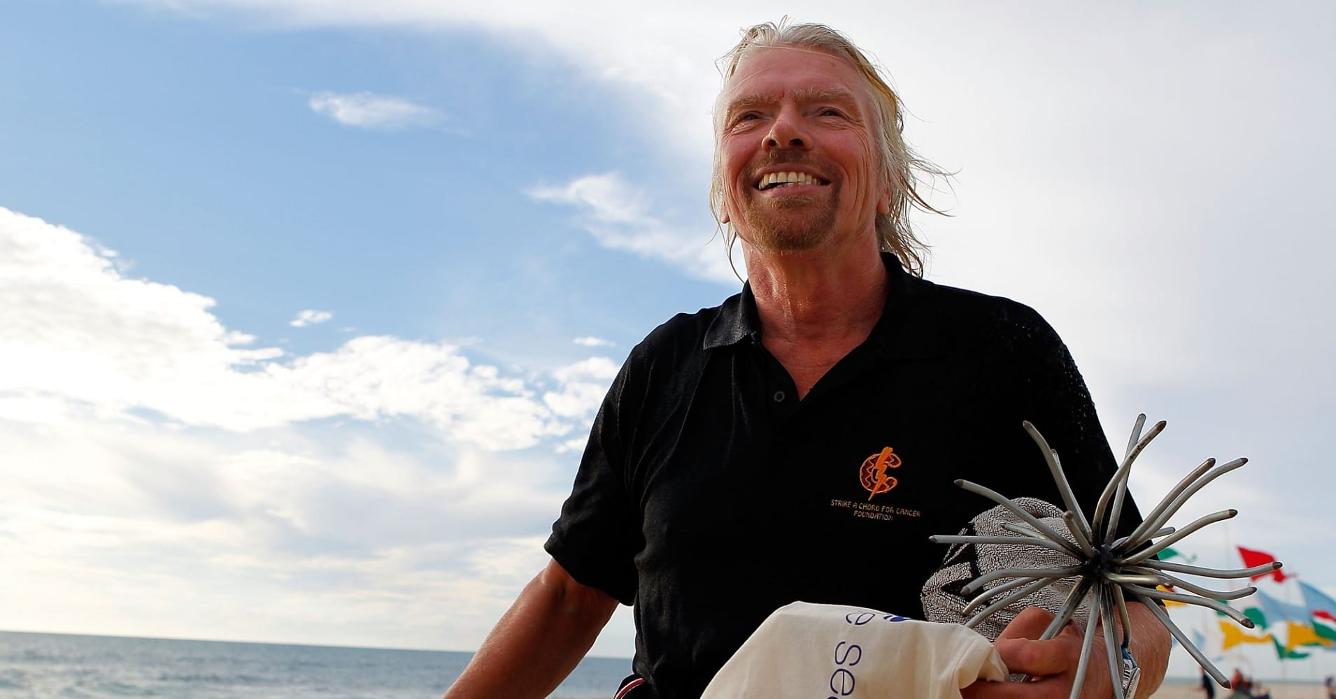 Sir Richard Branson walks up Cottesloe Beach after arriving by kite surfer.