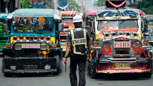 A busy street in Manila, featuring jeepneys and a traffic enforcer.