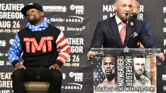 Floyd Mayweather Jr. (L) looks on as UFC fighter Conor McGregor speaks about their upcoming fight during a press call at the Staples Center in Los Angeles, California on July 11, 2017.