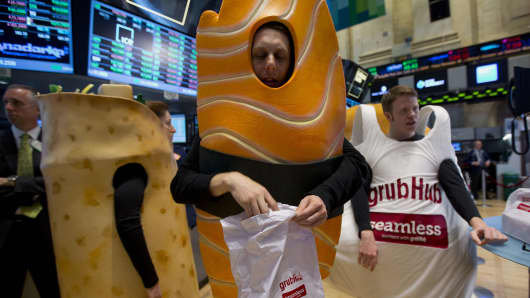 Actors dressed in Grubhub Inc. costumes interact with traders on the floor of the New York Stock Exchange (NYSE) in New York.