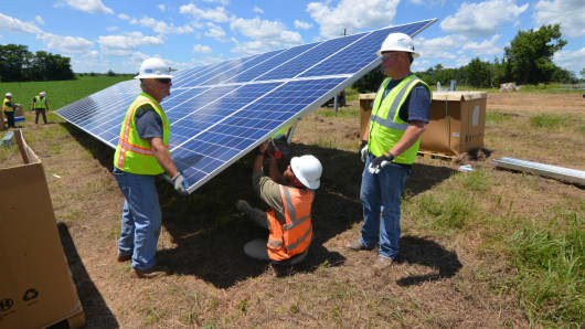 Workers install solar panels at East Kentucky Power Cooperative's 60-acre solar farm near Winchester, Kentucky. The farm will feature 32,300 panels capable of producing 8.5 megawatts of electricity.