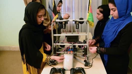 In this photograph taken on July 2, 2017, teenagers from the Afghanistan Robotic House, a private training institute, work on a robot at the Better Idea Organization center in Herat.