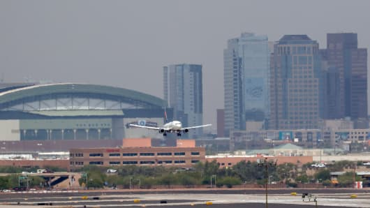 Heat waves ripple across the tarmac at Sky Harbor International Airport as downtown Phoenix stands in the background as an airplane lands June 20, 2017 in Phoenix.