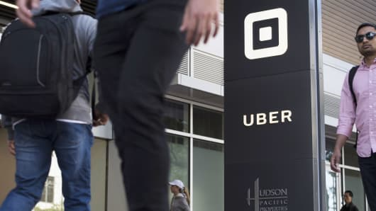 Pedestrians walk past the Uber Technologies headquarters building in San Francisco.