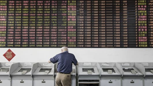 An investor stands at a trading terminal in front of an electronic stock board at a securities brokerage in Shanghai, China, on Friday, June 9, 2017.