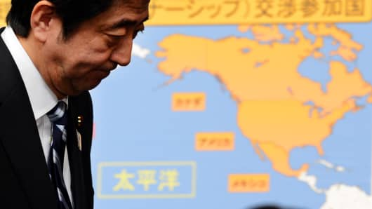 Japanese Prime Minister Shinzo Abe next to a map of the original Trans-Pacific Partnership participating countries.