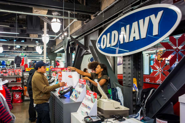 An employee hands a customer a shopping bag at an Old Navy Inc. store in San Francisco.