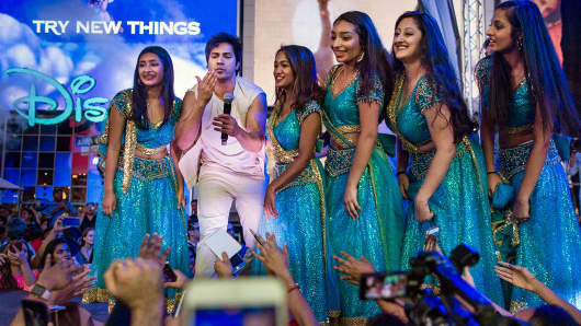 Varun Dhawan salutes his fans in between dancers wearing traditional Indian dresses during The 18th edition of the International Indian Film Academy (IIFA) awards weekend event at Times Square on Thursday, July 13, 2017, in New York.