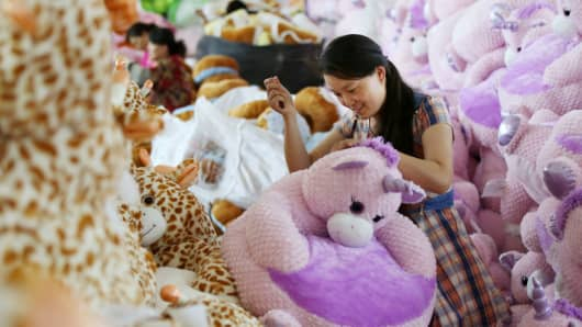 A woman makes toys at a factory in Ganyu, in China's eastern Jiangsu province on June 9, 2017.