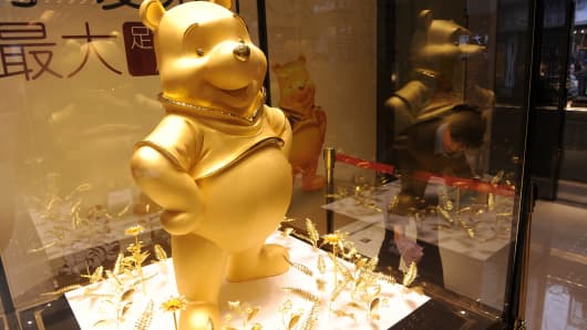 A gold figure of Winnie The Pooh is displayed inside a glass cabinet at a jewelry store on March 22, 2012 in Chengdu, China.