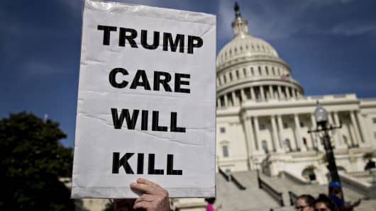 A demonstrator opposed to the Senate Republican health-care holds a sign that reads 'Trump Care Will Kill' while marching near the U.S. Capitol in Washington, D.C., U.S., on Wednesday, June 28, 2017.