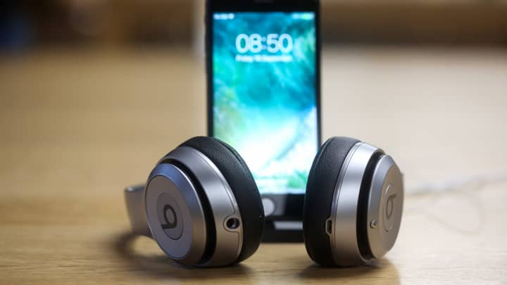 A pair of Beats by Dr. Dre Solo wireless headphones sit on display next to a new iPhone 7 smartphone.