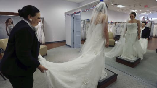 A woman tries on a wedding gown at Alfred Angelo Bridal.