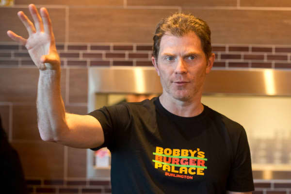 Bobby Flay describes his burgers during the opening of a location of Bobby's Burger Palace in the Burlington, Mass.