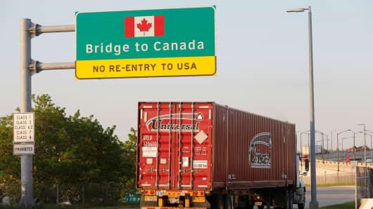 A semi truck headed for Windsor, Ontario, drives onto the Ambassador bridge in Detroit, Michigan.
