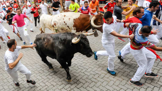People run with Nunez del Cuvillo's fighting bulls during the eighth day of the San Fermin Running of the Bulls festival in Pamplona, Spain.