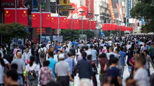Pedestrians walk past Chinese flags displayed along the Nanjing Road pedestrian street in Shanghai, China.
