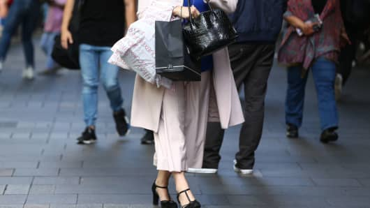 A woman carries shopping bags as she walks at the Pitt Street Mall in Sydney, Australia, on Thursday, April 13, 2017.