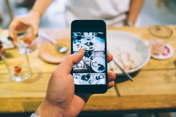 Capturing the snapshots of an enjoyable meal with friends by smartphone in a cafe.