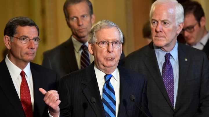 Senate Majority Leader Mitch McConnell (R-KY) , center, talks about working through part of the recess as senators John Barrasso (R-WY), left, John Thune (R-SC) and John Cornyn (R-TX) wait to talk about health care at the U.S. Capitol July 11, 2017 in Washington, DC.