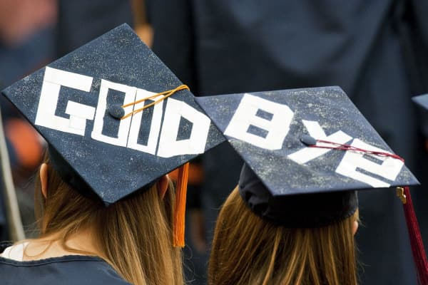 Two graduates display a farewell message on their mortarboards during Syracuse University's commencement ceremony
