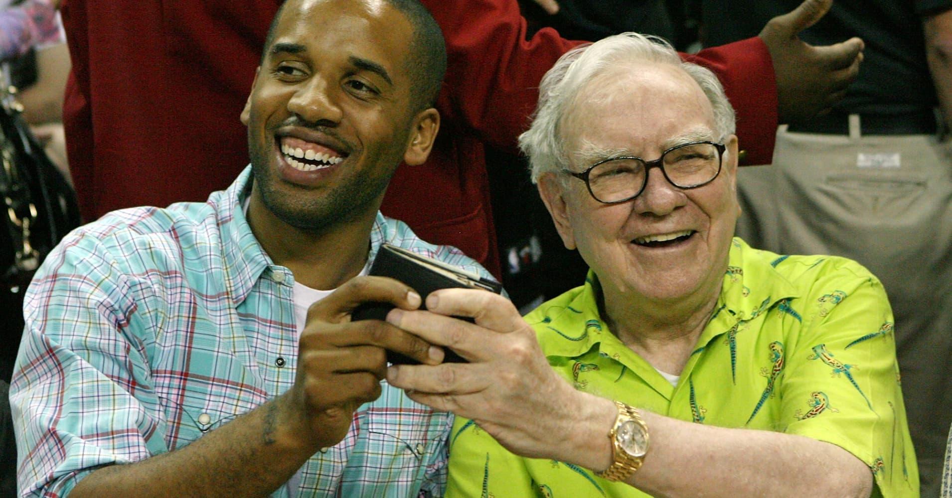 Maverick Carter and Warren Buffett joke around courtside with Buffett's wallet during the 2008 State Farm Basketball Challenge exhibition game.