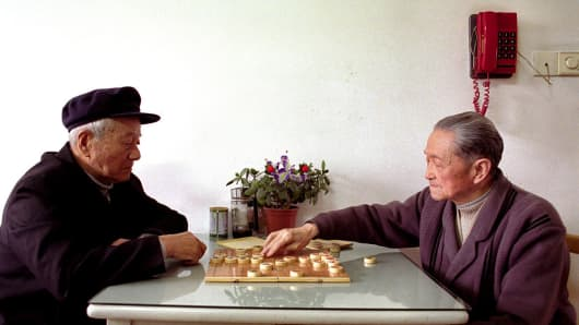 Two men play Chinese chess in an elderly home in the Huang Pu district.