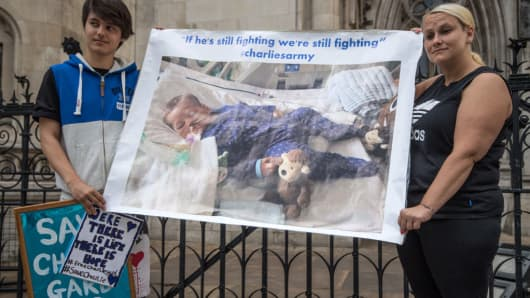 Supporters of Chris Gard and Connie Yates, parents of terminally ill baby Charlie Gard, hold a banner outside The Royal Courts of Justice on July 13, 2017 in London, England.