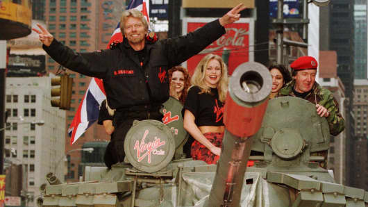 Richard Branson (L), chairman of Virgin, waves as he rides a tank into New York's Times Square to promote the United States launch of Virgin Cola, May 12. Virgin Cola was introduced in the United Kingdom in 1994, and is also available in several other European countries.