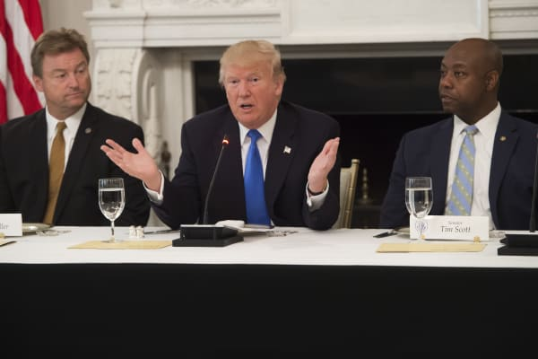 President Donald Trump speaks alongside US Senator Dean Heller (L), Republican of Nevada, and US Senator Tim Scott (R), Republican of South Carolina, during a meeting with Republican Senators to discuss the health care bill in the State Dining Room of the White House in Washington, DC, July 19, 2017.