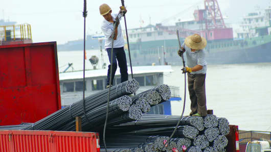 Two workers load steels products at a wharf in Yichang, China.