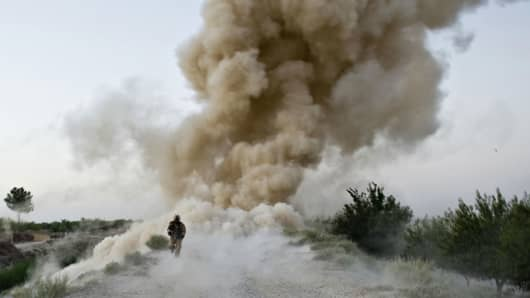 A US Marine of 2nd Marine Expeditionary Brigade runs to safety moments after an IED blast in Garmsir district of Helmand Province in Afghanistan on July 13, 2009.