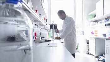 Male scientist using pipettes in biology laboratory