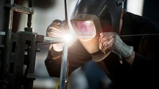 An employee welds a specialized metal product in the shop at the Amuneal Manufacturing plant in Philadelphia, Pennsylvania.