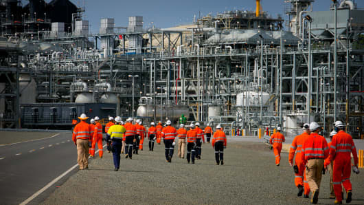 Workers walk towards a plant at the Queensland Curtis Liquefied Natural Gas (QCLNG) project site in Gladstone, Australia, on Wednesday, June 15, 2016.