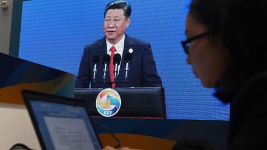 A journalist works in front of a live feed of China's President Xi Jinping speaking at the opening ceremony of the Belt and Road Forum, on a screen in the media center of the China National Convention Center, the forum's venue, in Beijing on May 14, 2017.