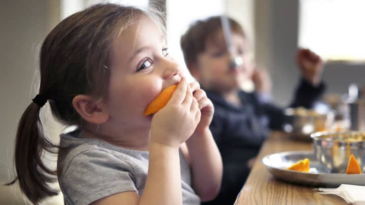 Camille Pitzer, 3, bites into a freshly sliced orange at MaineLy Childcare -- one of several local daycares working to improve the food it serves.