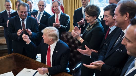 President Donald Trump hands Andrew N. Liveris, CEO of Dow Chemical, the pen after signing an executive order about regulatory reform in the Oval Office of the White House February 24, 2017 in Washington, DC.