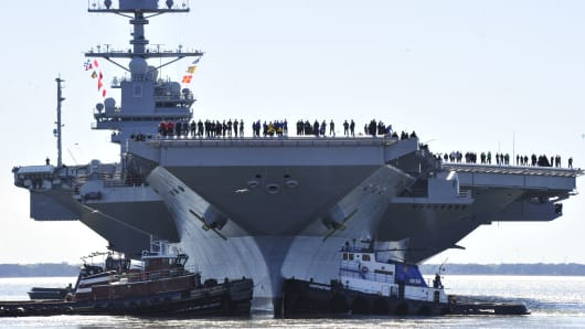 In this handout photo provided by the U.S. Navy, sailors aboard the aircraft carrier Pre-Commissioning Unit (PCU) Gerald R. Ford (CVN 78) man the rails as the ship departs Huntington Ingalls Industries Newport News Shipbuilding for builder's sea trials off the U.S. East Coast on April 8, 2017 in Newport News, Virginia.