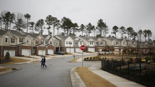 Pedestrians pass in front of residential buildings in the KB Home Glencroft neighborhood of Cary, North Carolina.