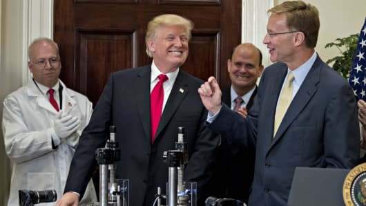 President Donald Trump, center, smiles after participating in a glass strength test of a Corning Valor vial with Wendell Weeks, chairman and chief executive officer of Corning Inc., right, during an announcement on a new pharmaceutical glass packaging initiative in the Roosevelt Room of the White House in Washington, D.C., U.S., on Thursday, July 20, 2017.